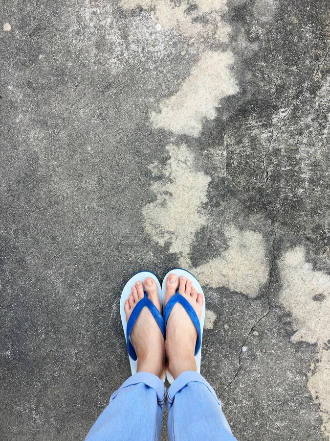 Blue Flip Flop on Cement Floor,Top view. Beautiful Woman Wearing Blue Shoes and Jeans of Accessory on Concrete Background. Great For Any Use stock images