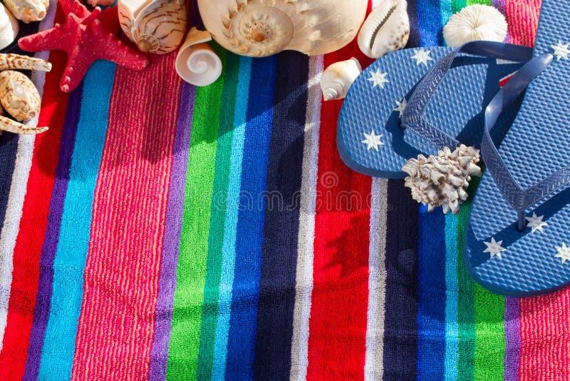 Blue flip flops on beach towel stock photos