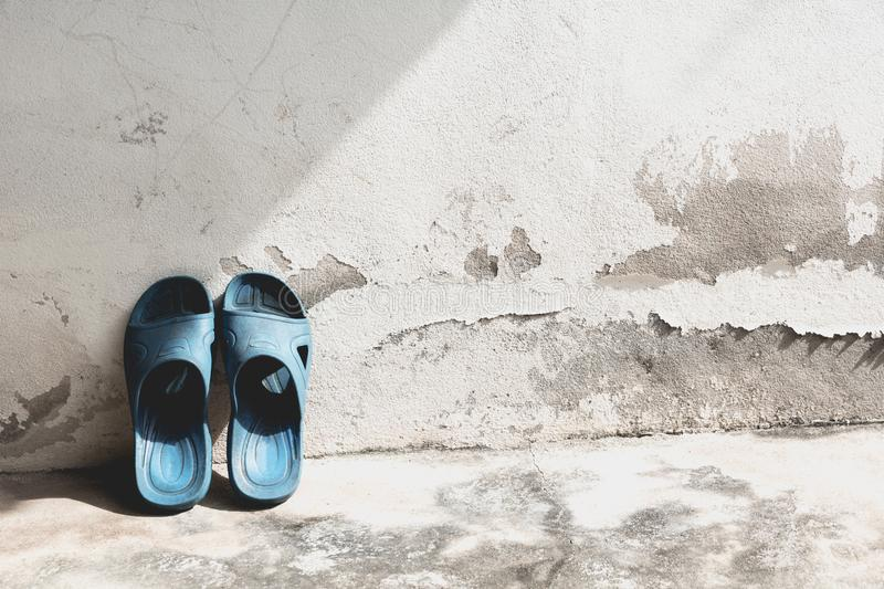 Blue flip flops on the old concrete wall. stock photography