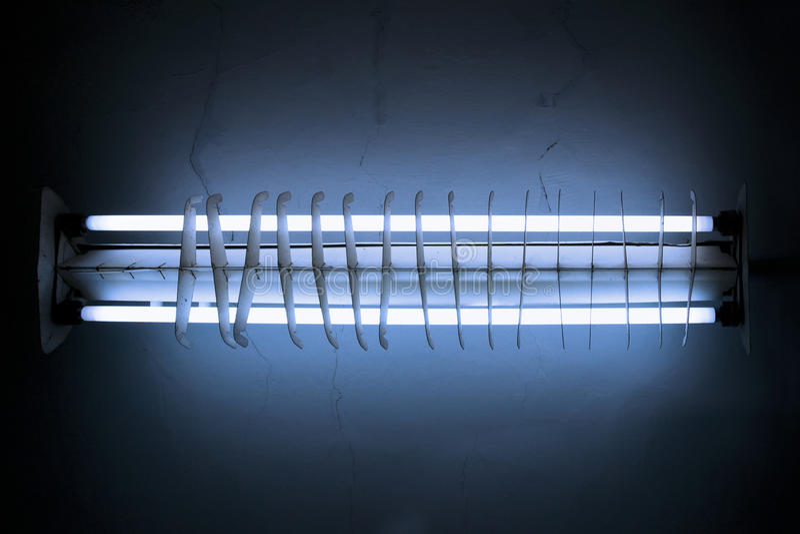 Blue fluorescent light tube. Old blue fluorescent light tube shining ray on dark background stock photography