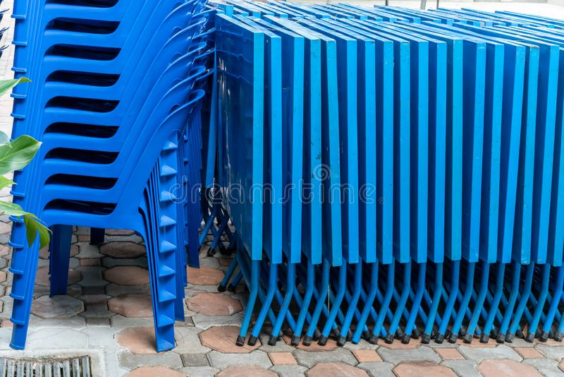 Blue foldable tables and plastic chairs stacked outside on concrete blocks stock photos