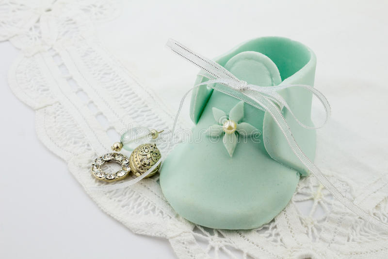 Blue fondant sugar shape baby bootees and silver charms on white lace background royalty free stock image