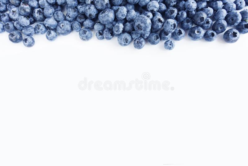 Blue food on a white background. Ripe blueberries at border of image with copy space for text. Various fresh summer berries on whi stock image