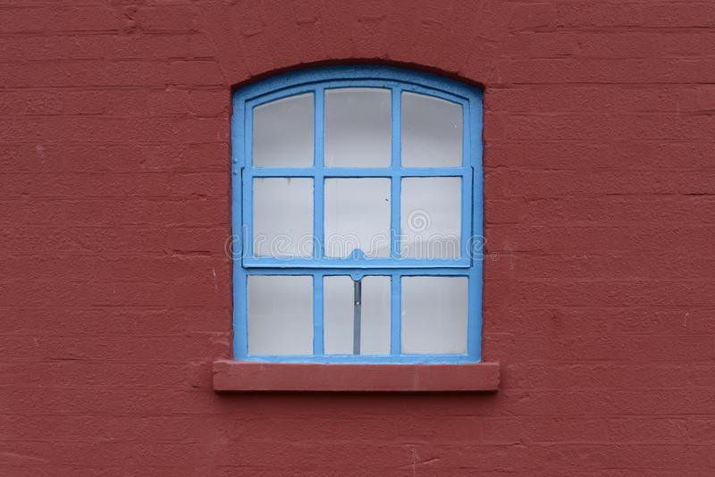 Blue Framed Window with Arch in a Brick Wall royalty free stock photography
