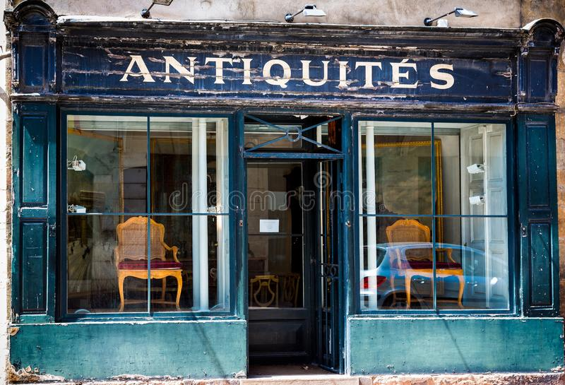 Blue French antique shop front with flaking paint in Beaune, Burgundy. France on 17 June 2013 stock photos