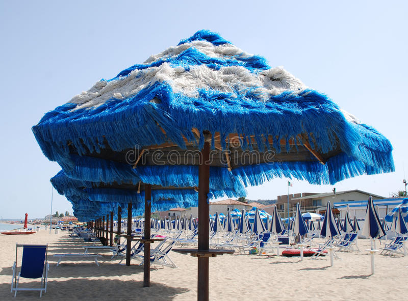Blue Fringed Beach Umbrellas. Blue and white fringed beach umbrellas on a beach on a sunny summers day stock image