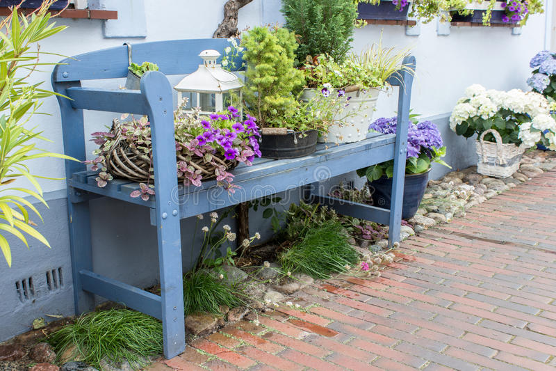 Blue garden bench. In front of the house with flowers and decoration royalty free stock photo
