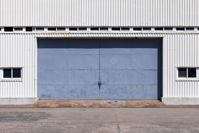 Blue gate in white metal warehouse wall. Closed blue gate in white ridged metal warehouse wall, flat background photo texture royalty free stock photo