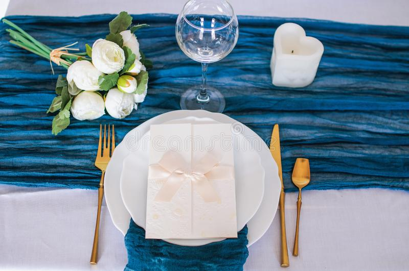 Blue gauze runner for weddings events. Wooden table is covered with a color runner tablecloth with a white plate and cutlery royalty free stock photography
