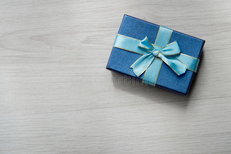 Blue gift box on gray wooden texture background with copyspace f. Or text stock photography