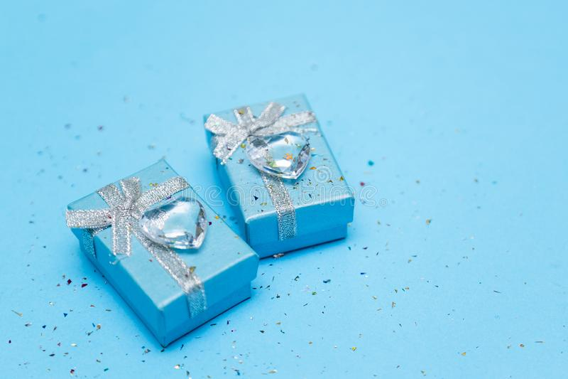 Blue gift box with jewelry and crystal heart, around sequins. Blue background. stock images