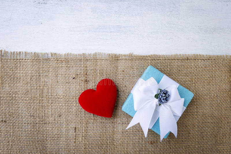 Blue gift box with red heart on hessian fabric. With space on white wood background, Valentine`s concept royalty free stock image
