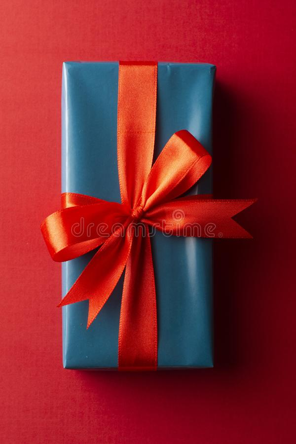 Blue gift box with red ribbon and bow isolated on red background, top view. Christms, party concept. Blue gift box with red ribbon and bow isolated on red royalty free stock images