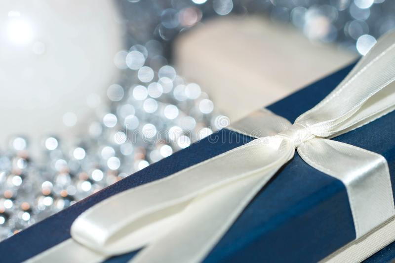 Blue gift box among silver Christmas decorations stock images