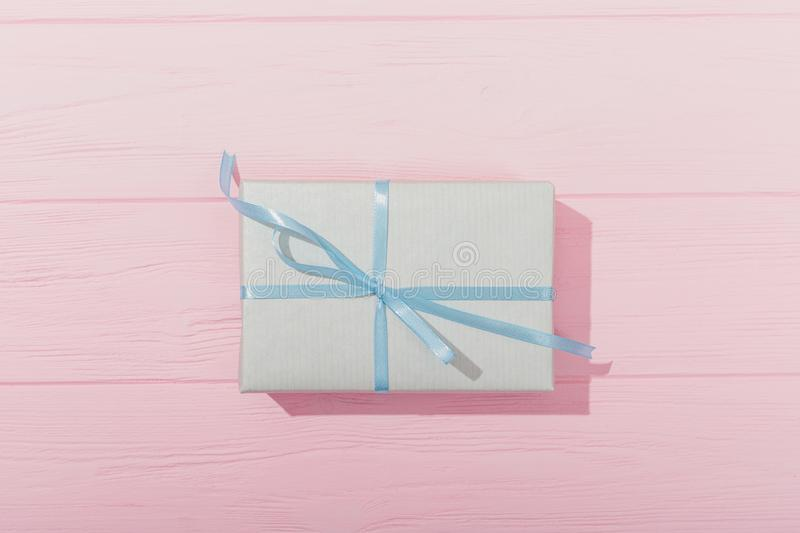 Blue gift box tied with satin ribbon on pink wooden background stock photos