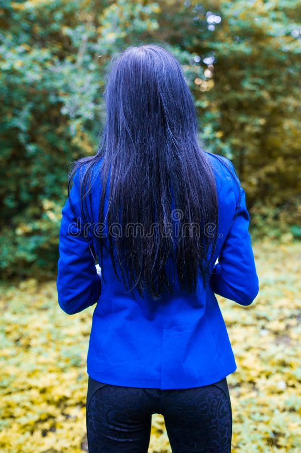 Blue girl from the back. Beautiful woman walking in the dark forest. Back view. blue long hair back view royalty free stock photos
