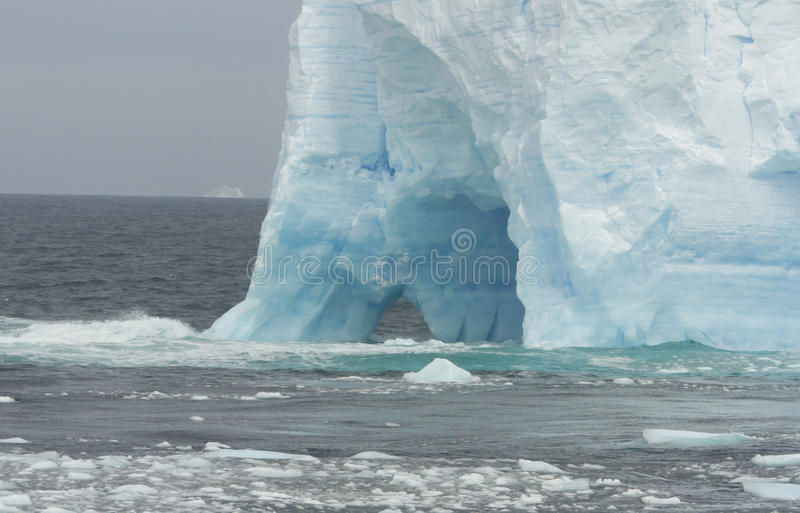 Blue glacial iceberg in Antarctica. Floating blue glacial iceberg in Antarctic waters with bergie bits and growlers royalty free stock photos