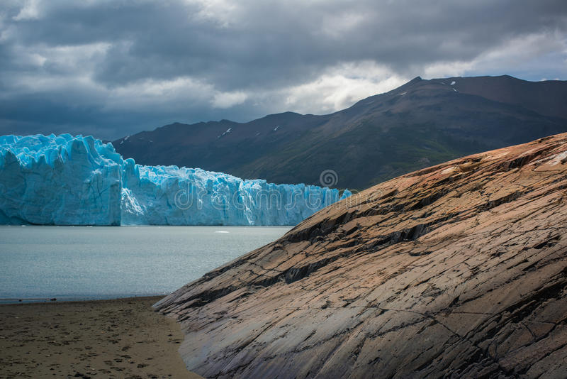 Blue glacier in the background of the mountains near the bay. Shevelev. royalty free stock photography
