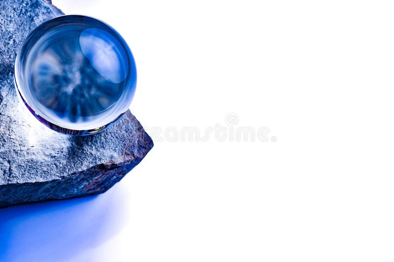 Blue glass ball on a stone stock photo