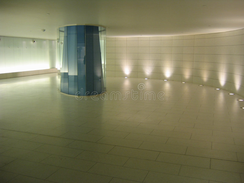 Blue glass colomn in an underground corridor stock photography