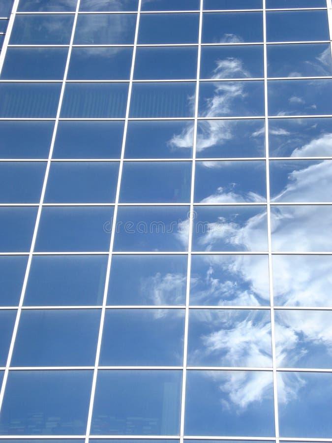 Blue glass facade reflecting white cloud stock photos