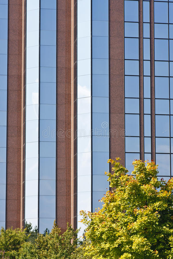 Blue Glass and Red Stone Behind Fall Foliage. A blue glass and red stone building behind colorful fall foliage stock photos