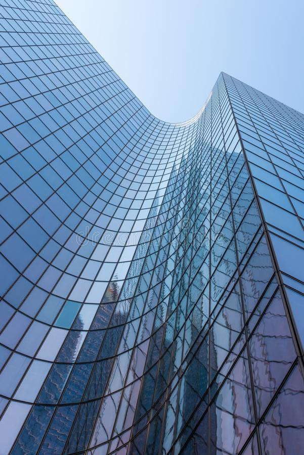Blue glass skyscraper facade against sky. Blue glass skyscraper facade reflections against sky royalty free stock images