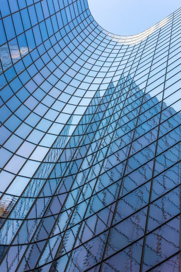 Blue glass skyscraper facade against sky. Blue glass skyscraper facade reflections against sky royalty free stock image