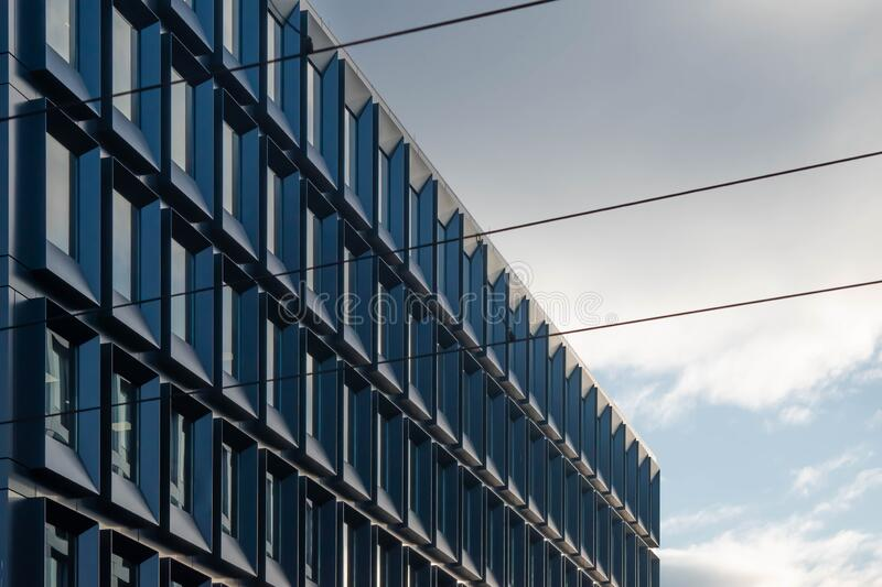 Blue glass wall with windows of modern building. Abstract perspective. Blue color royalty free stock photography