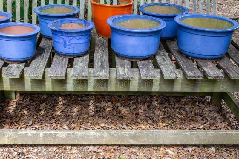 Blue glazed pots on open slat table, copy space. Horizontal aspect royalty free stock image