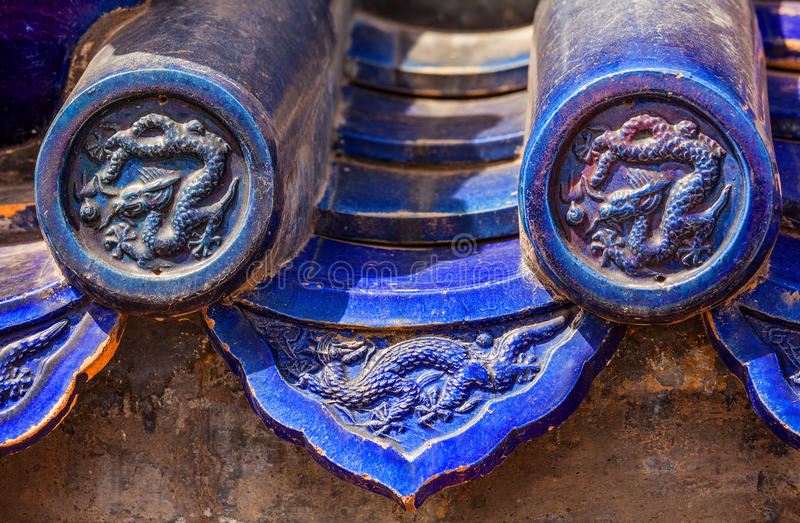 Blue glazed tiles with traditional chinese imperial dragons. Blue glazed tiles of roof eaves decorated traditional chinese imperial dragons on ancient temple stock photography