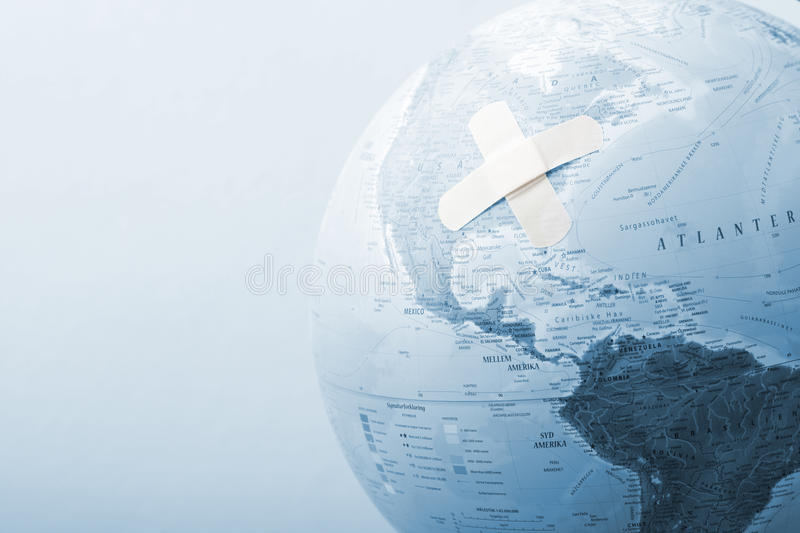 Blue globe with bandages. A view of a pale blue globe with crisscrossed bandages on it. Possible theme: Financial crisis stock photos