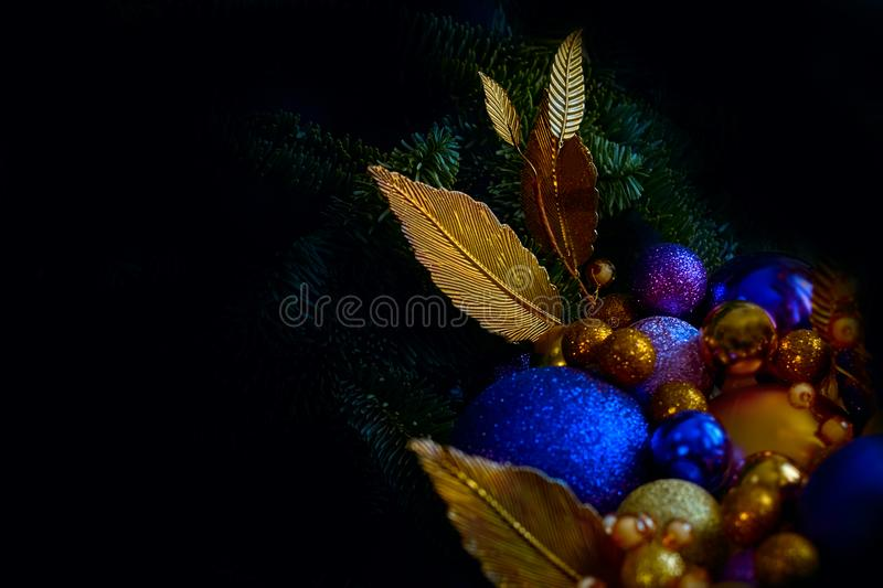 Blue and golden Christmas balls on a christmas tree closeup view in a low key with a copy space.  royalty free stock image