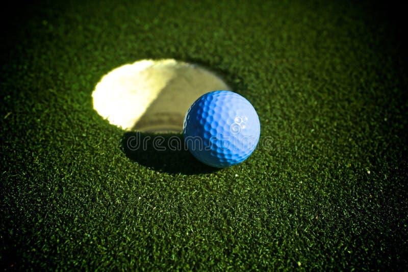 Blue golf ball golf course hole stock image