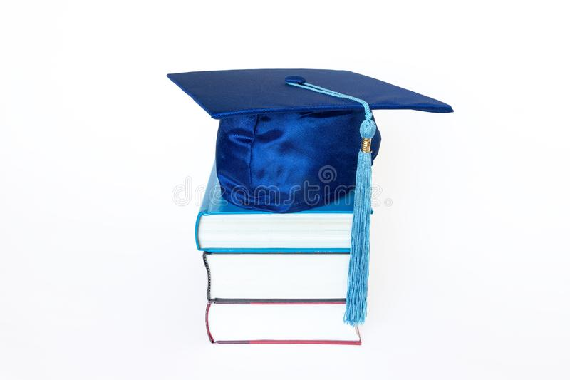 Graduation Cap With Tassel on Books Isolated on White Background. Blue graduation cap with tassel on top of books isolated on white background. Education concept stock photo