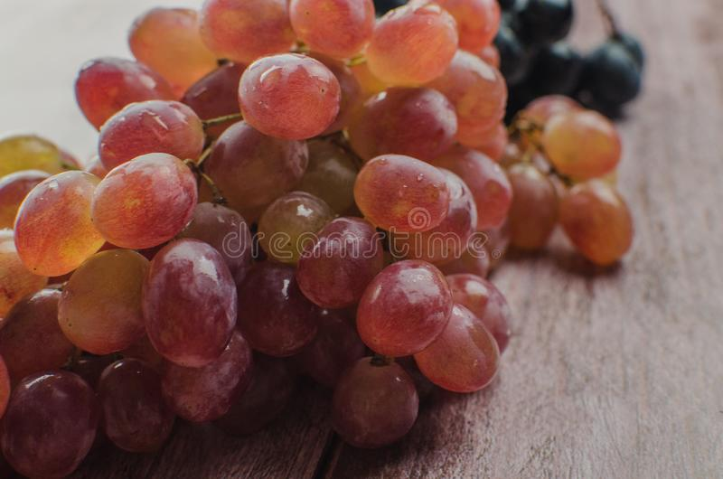 Blue grapes with green leaf healthy eating,. On wood background royalty free stock image