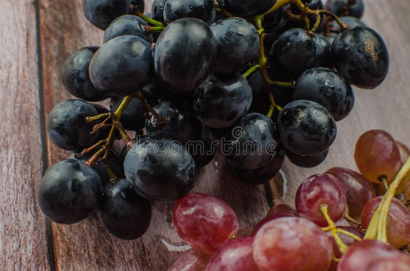 Blue grapes with green leaf healthy eating, isolated. On wood background royalty free stock photo