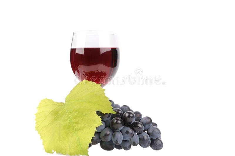 Blue grapes with leaf and wine in the glass. Alcohol, background, bar, beverage, blank, cabernet, celebration, clean, clear, drink, elegance, food, full stock photography