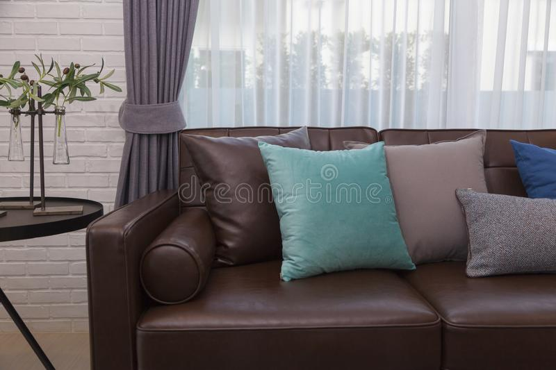 Blue and gray pillows on leather sofa in modern living room stock photos