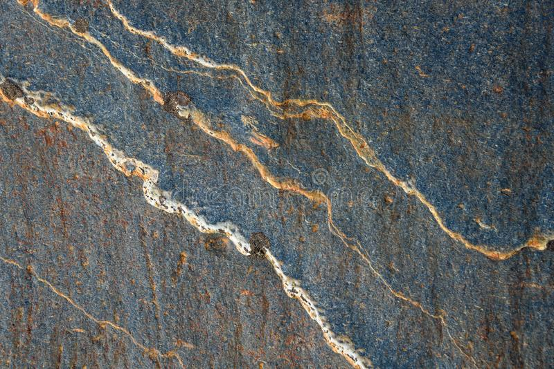 Blue gray stone with white and orange lines of pattern and texture as a nature background stock image