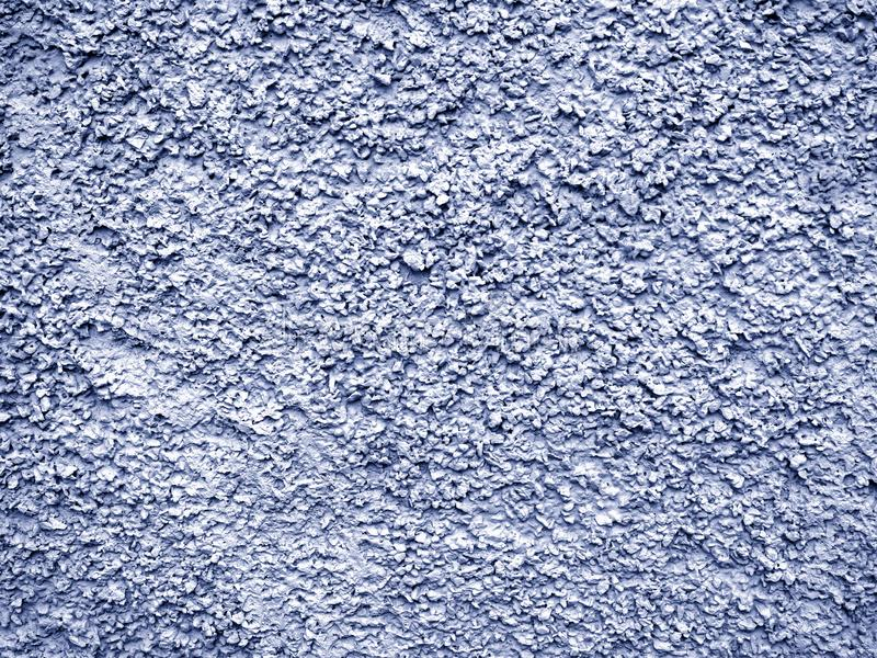 Blue-gray stucco with a chaotic convex pattern. The stone wall is covered with new rough plaster royalty free stock image