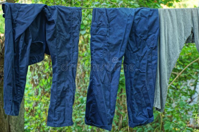 Blue and gray wrinkled pants dry on a wire royalty free stock photography