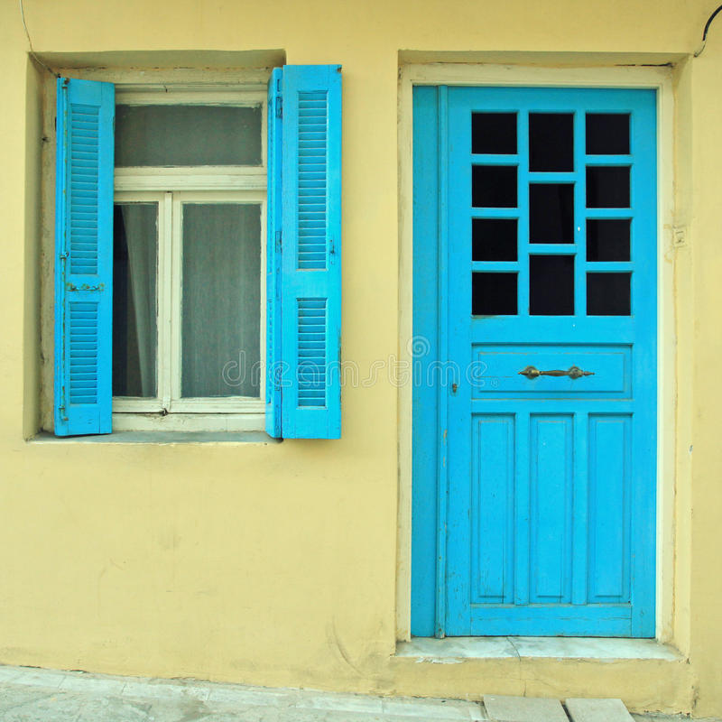 Blue greek shutters window and door in old house stock photography