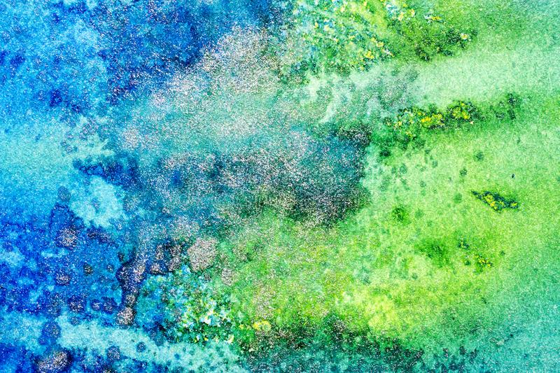 Blue and Green Abstract Metallic Background. Close up photograph of a handmade abstract background featuring shades of blue and green with flecks of silver inks royalty free stock photos