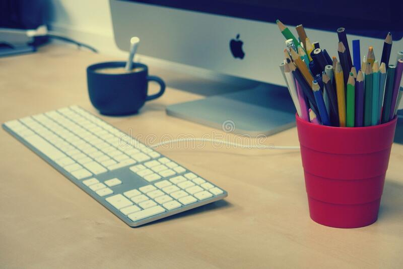 Blue Green and Black Colored Pencils on Red Plastic Cup Beside Silver Imac royalty free stock photography