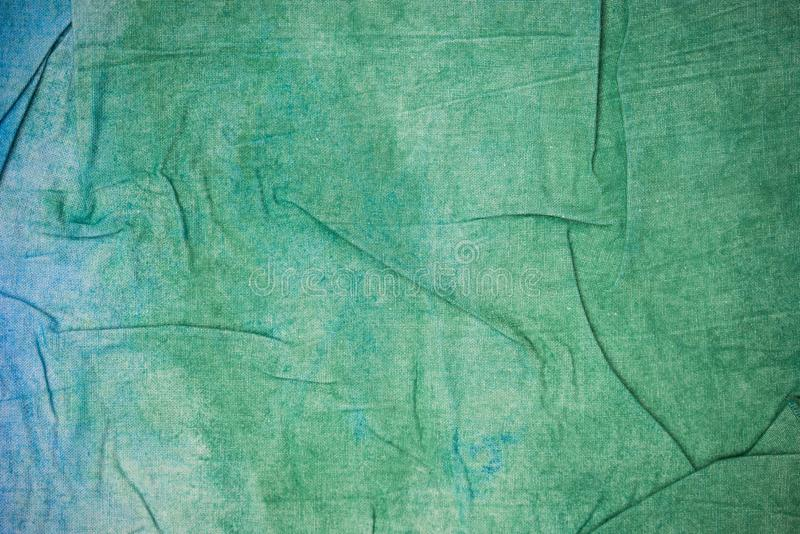 Blue and green creased painted textile background. Blue and green color painted textile background stock photos