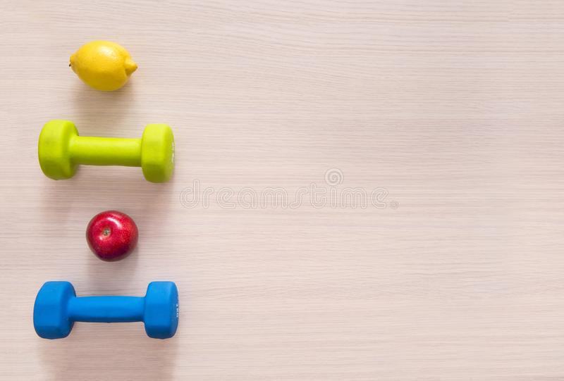 Blue and green dumbbells, red Apple, yellow lemon top view, flat. Blue and green dumbbells, red Apple, yellow lemon flat lay top view stock photography