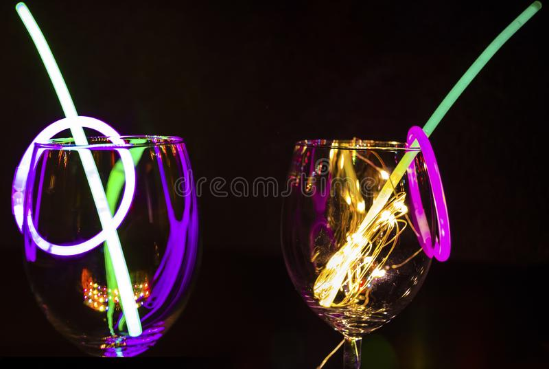 Blue and green glow stick on a wine glass with new year celebration with colorful light relection aginst the dark background party stock photo