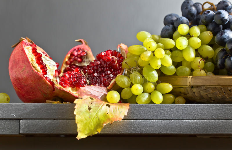 Blue and green grapes with pomegranate stock photography