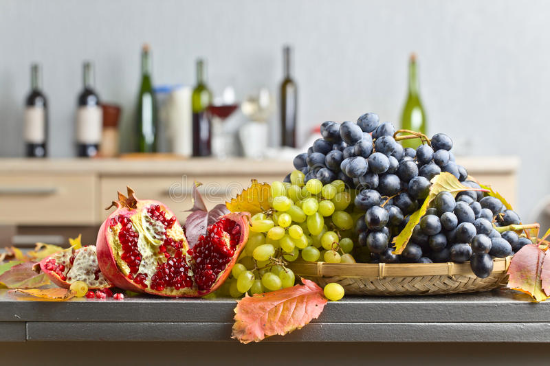 Blue and green grapes with pomegranate royalty free stock photo
